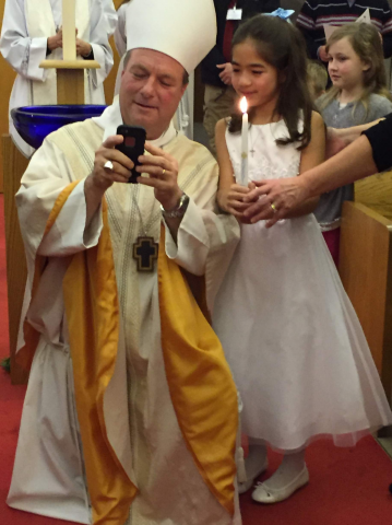 Bishop Rickel taking a selfie at a Baptism